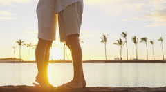 Kissing couple romantic at sunset on vacation taking selfie in love at beach Arkistovideo