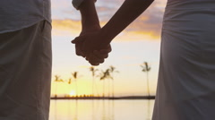 Romantic couple holding hands on beach at sunset Stock Footage
