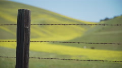 Medium shot of a barbed wire fence near a ranch - stock footage