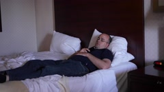 Man falls asleep while watching TV on a hotel bed - stock footage