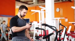 Man listen to music and riding stationary bike in the gym taking selfie Stock Footage