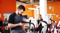 Man listen to music and riding stationary bike in the gym chatting cellphone Stock Footage