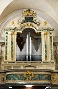 Organ and choir loft above the entrance of the church. Stock Photos