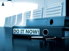 Do it Now on File Folder. Blurred Image - stock illustration
