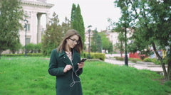 Pretty girl listening to the music win earphones outdoor 4k Stock Footage
