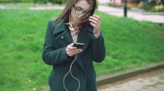 The girl in green coat listening to the music from phone in windy day 4k Stock Footage