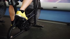Side view close-up part of young man in sports shoes cycling at gym. slider shot - stock footage