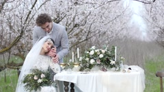 Just married bride and groom a romantic dinner in the lush flowered garden Stock Footage
