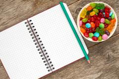 Spiral notebook and bowl with candies - stock photo