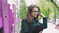 Fine girl holding a tablet, wearing glasses and smiling on street background 4k - stock footage