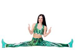 young woman sit on twine and stretching, showing fingers up, sign OK. - stock photo