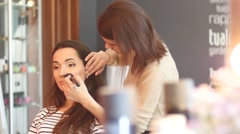 Make up for young beautiful bride in beauty salon - applying powder bruch - stock footage