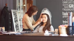 Pretty woman stylist doing make up in beauty salon for young bride - stock footage