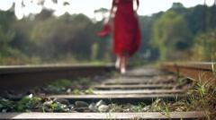 Woman in red, walking on railway tracks Stock Footage