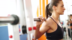 Close up of young woman with barbell flexing muscles in gym with smart watch Stock Footage