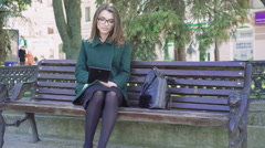 Style girl sitting on a bench, using a tablet on the street. 4K - stock footage