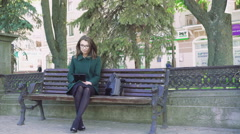 Style girl sitting on a bench, taking photo with a tablet outdoor. 4k - stock footage
