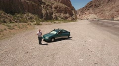 A man lands his drone in a desert canyon road Stock Footage