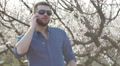 Bearded man talking on mobile cell phone outdoors in a blooming trees background Footage