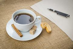Cup of coffee, cookie, pen and paper on sackcloth background - stock photo