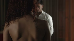 A couple in a intimal moment. The woman takes off his shirt Stock Footage