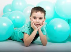 Young man lying on the floor, around him are balloons Stock Photos