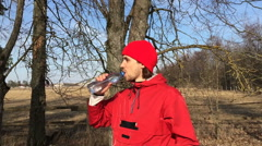 Sportsman drinks water from a bottle in the open air Stock Footage