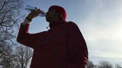 Silhouette of sportsman drinks water from a bottle Stock Footage