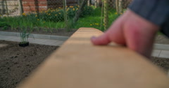 Placing a wooden board on a garden bed Stock Footage