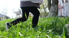 Kid child legs running on a park grass having fun slow motion low camera Stock Footage
