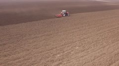 Tractor cultivating arable land for seeding crops, aerial view Stock Footage