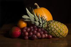 Variety of fruits on a wooden table, studio picture Stock Photos