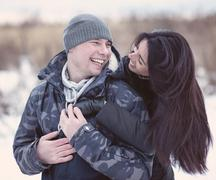 Beautiful young couple hugging and smiling in winter park. Happy family Stock Photos
