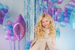 Portrait of Pretty little girl sits in a studio with a lot of colour baloons Stock Photos