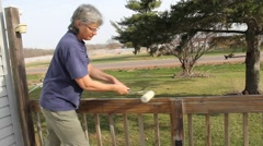 Woman staining a patio deck Stock Footage