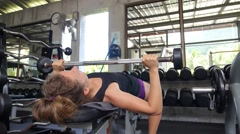 Sporty Woman Lifting Weight in Gym. Exercise and Fitness - stock footage