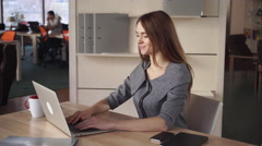 Woman sitting at the working place works with laptop than close it and relax Stock Footage