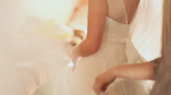 Mother helps the bride to wear a wedding dress - stock footage