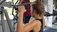 Sporty Young Woman Training in Gym. Exercise for Back and Shoulders Stock Footage