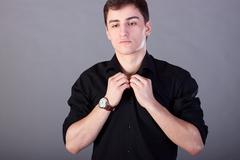Young guy businessman in a black shirt, fashion style, youth direction, concept Stock Photos