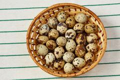 Several quail eggs lie in a basket with weak shadow - stock photo