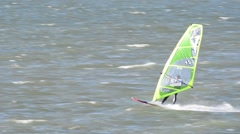 Windsurfer surfing fast and executing a forward loop at sea Stock Footage