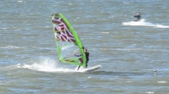 Windsurfer surfing fast and executing a shaka at sea Stock Footage