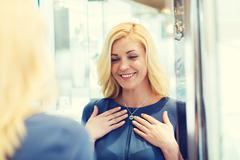 happy woman choosing pendant at jewelry store - stock photo