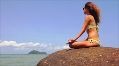 Yoga meditation on the stone at the beach - stock footage