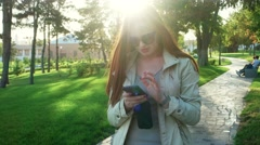 Young laughing adorable redhead student woman in coat holding her smartphone and Stock Footage