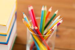 Stock Photo of close up of crayons or color pencils and books