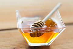 Close up of honey in glass bowl and dipper Stock Photos