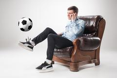 The portrait of fan with ball, holding  tv remote on white background - stock photo