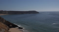4k Surfers wating wave beautiful coastline cliffs beach Sagres Portugal Stock Footage